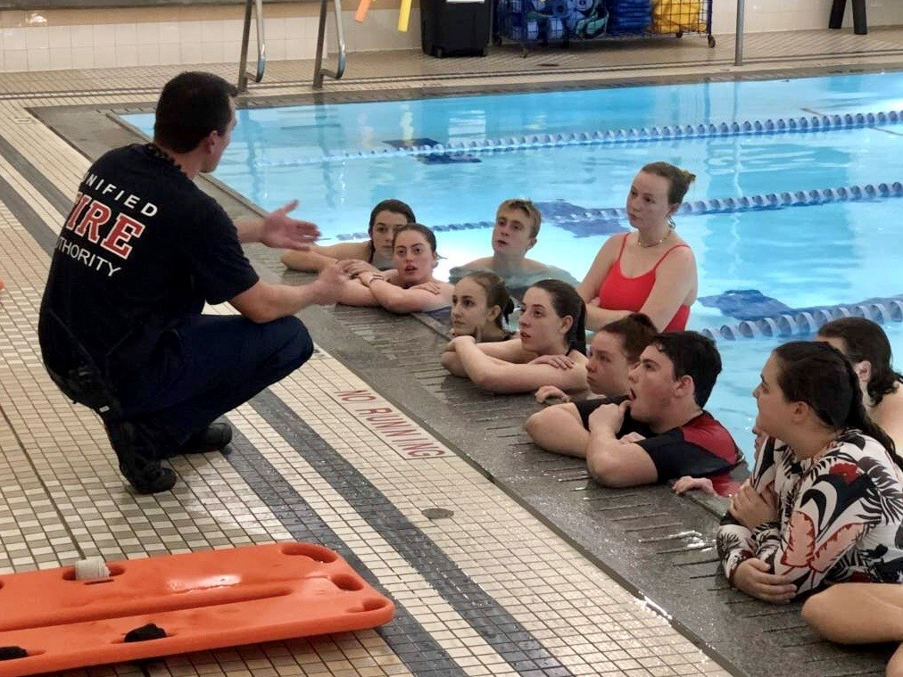Firefighter talking to swimmers in pool