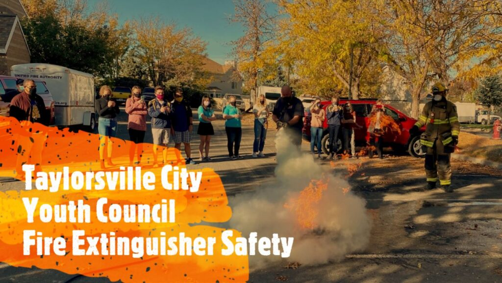"""""""Taylorsville City Youth Council Fire Extinguisher Safety"""" firefighter sprays fire with fire extinguisher"""